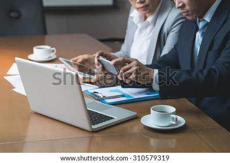 Cropped image of business people watching video on smartphone at the meeting