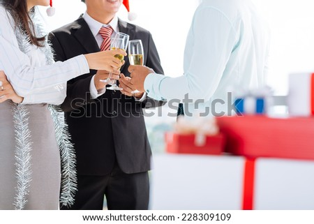 Cropped image of business team clinking at the Christmas party - stock photo