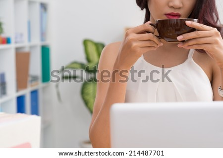 Cropped image of business woman drinking coffee while working on the laptop - stock photo