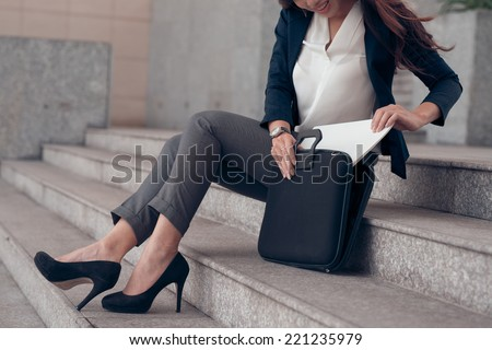 Cropped image of business woman getting documents out of briefcase while sitting on the steps - stock photo