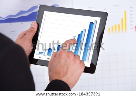 Cropped image of businessman analyzing bar graph on digital tablet in office