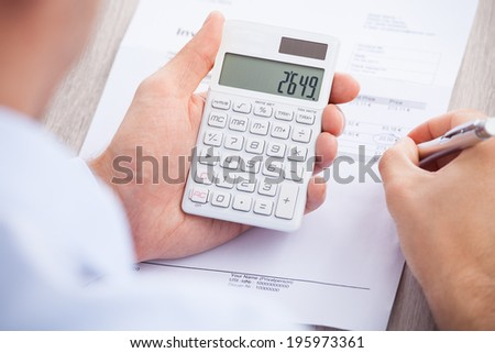 Cropped image of businessman calculating invoice at desk - stock photo