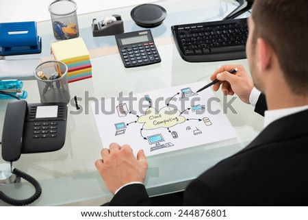 Cropped image of businessman drawing cloud computing chart at desk in office - stock photo