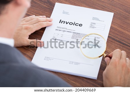 Cropped image of businessman examining invoice with magnifying glass at desk - stock photo