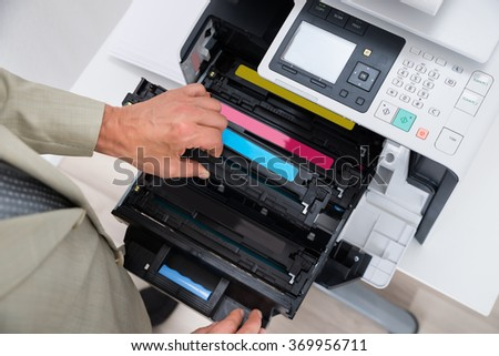 Cropped image of businessman fixing cartridge in photocopy machine at office - stock photo