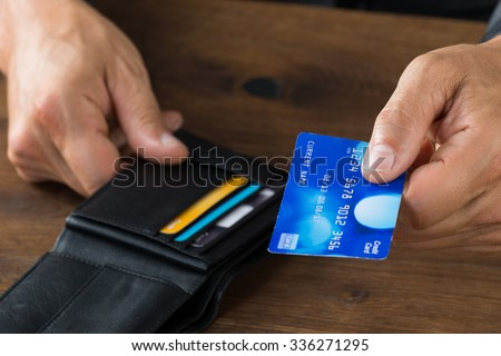 Cropped image of businessman giving credit card from wallet at desk - stock photo