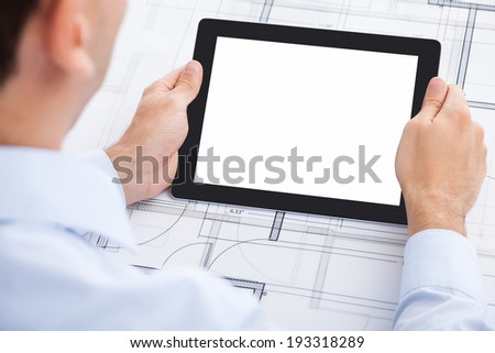 Cropped image of businessman holding blank digital tablet over blueprint in office