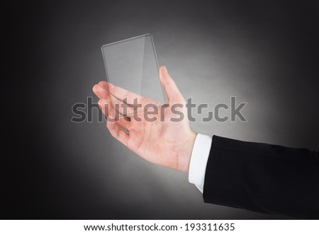 Cropped image of businessman holding smartphone against black background - stock photo