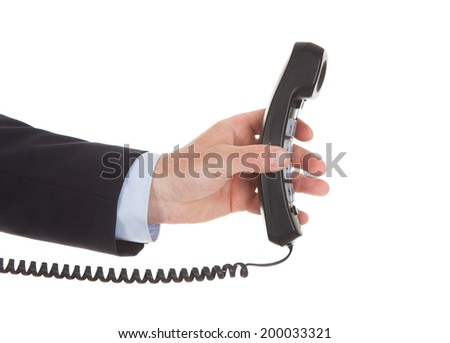 Cropped image of businessman holding telephone receiver over white background - stock photo