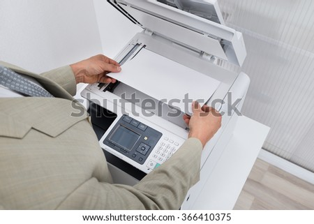 Cropped image of businessman keeping paper on photocopy machine in office