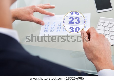 Cropped image of businessman looking at calendar through magnifying glass at desk - stock photo