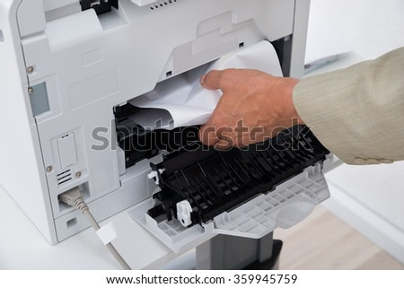 Cropped image of businessman's hand removing paper stuck in printer at office - stock photo
