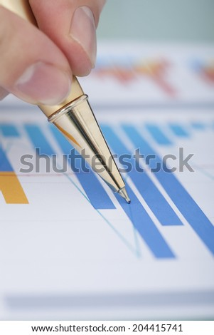 Cropped image of businessman's hand showing diagram on financial report with pen - stock photo