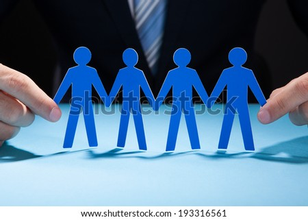 Cropped image of businessman's hands holding paper people chain on desk - stock photo