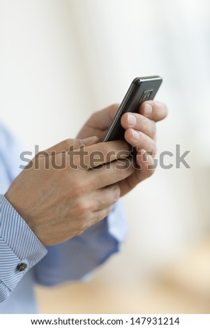 Cropped image of businessman's hands using smart phone in office