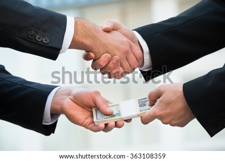 Cropped image of businessman shaking hand while bribing partner outdoors - stock photo