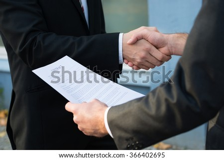 Cropped image of businessman shaking hands with partner while holding contract papers - stock photo