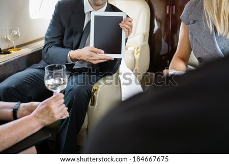Cropped image of businessman showing digital tablet to colleagues in private jet - stock photo