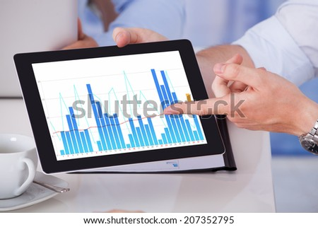 Cropped image of businessman showing graph on digital tablet to colleagues in office