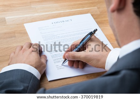 Cropped image of businessman signing contract document at office desk