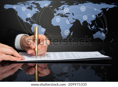 Cropped image of businessman signing contract with world map in background.  - stock photo