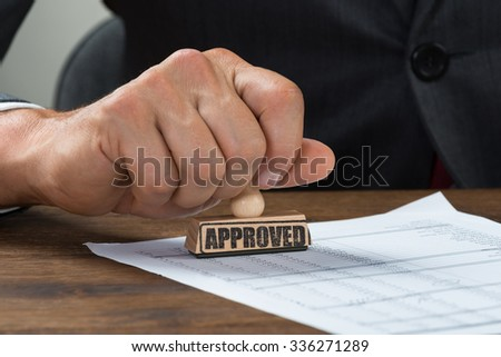 Cropped image of businessman stamping document marked with approved at desk - stock photo