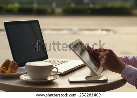 Cropped image of businessman using cellphone, laptop and digital tablet while sitting in a cafe, selective focus - stock photo