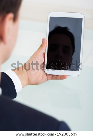 Cropped image of businessman using digital tablet at desk in office - stock photo