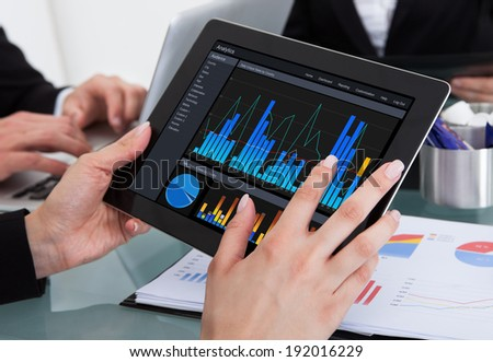 Cropped image of businessman using digital tablet with colleagues at desk in office - stock photo