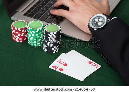 Cropped image of businessman using laptop by stacked poker chips and cards at desk in office - stock photo