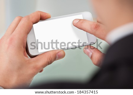 Cropped image of businessman using smart phone in office - stock photo