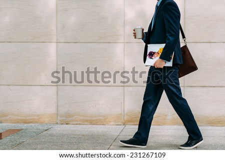 Cropped image of businessman with coffee and magazine going to work - stock photo
