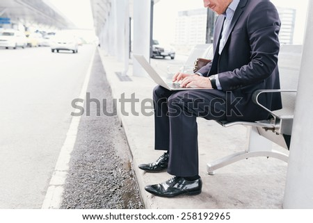 Cropped image of businessman working on laptop while sitting at the airport terminal - stock photo