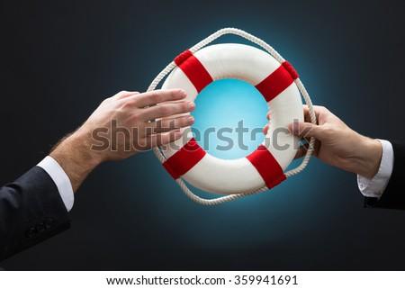Cropped image of businessmen passing lifebuoy over blue background - stock photo