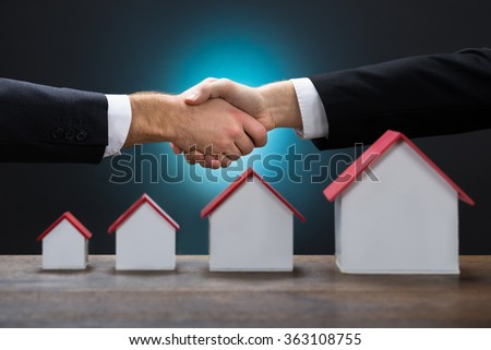 Cropped image of businessmen shaking hands by various size of house models against blue background - stock photo