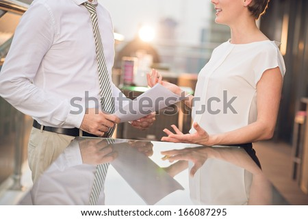 Cropped image of businesspeople gesturing while talking on the foreground - stock photo