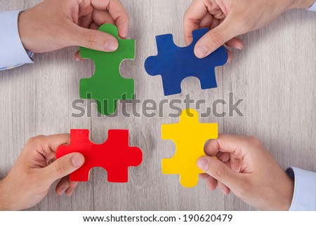 Cropped image of businesspeople joining multicolored puzzle pieces at desk in office - stock photo