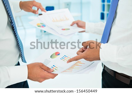 Cropped image of businesspeople pointing at the business graphics on the foreground - stock photo