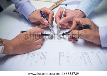Cropped image of businesspeople pointing with pens at something in the business document on the foreground  - stock photo