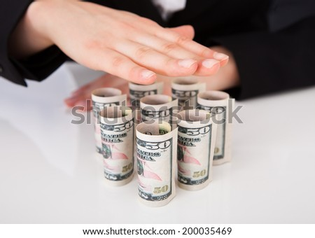 Cropped image of businesswoman shielding rolled dollar bills at office desk