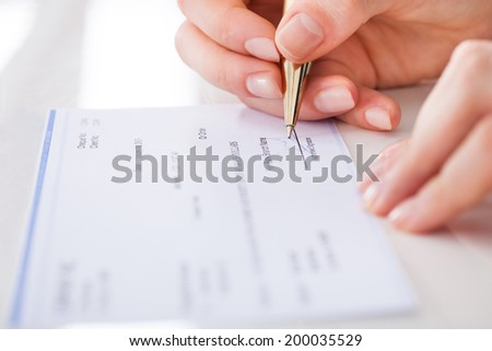 Cropped image of businesswoman signing cheque at desk - stock photo