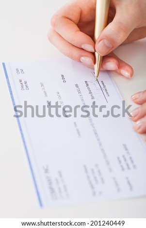 Cropped image of businesswoman signing cheque at desk