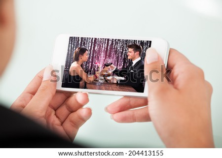 Cropped image of businesswoman watching couple toasting wineglasses on cellphone over white background - stock photo