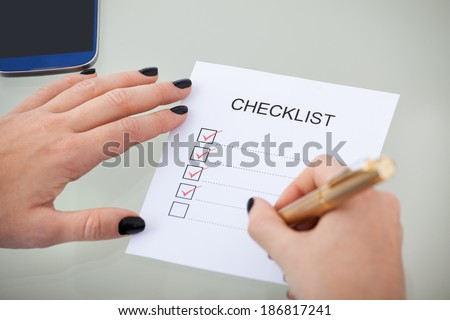 Cropped image of businesswoman with checklist at desk in office - stock photo