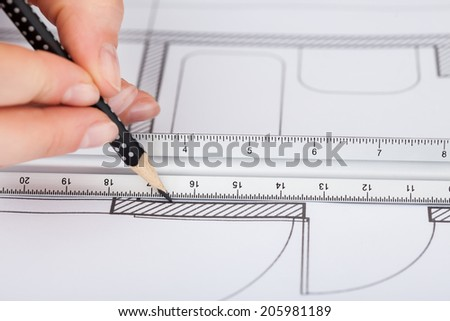 Cropped image of businesswoman working on blueprint at desk in office - stock photo