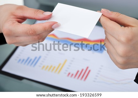 Cropped image of businesswomen exchanging business card at desk in office - stock photo