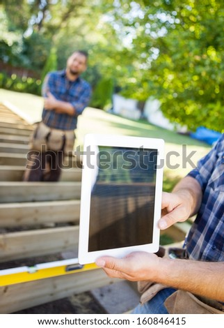 Cropped image of carpenter holding digital tablet with coworker in background at site - stock photo