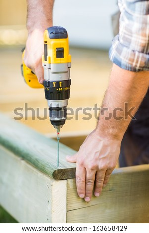 Cropped image of carpenter's hands using drill on wood at construction site - stock photo