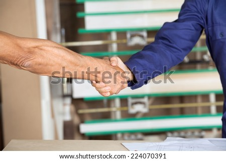 Cropped image of carpenter shaking hands with colleague in workshop - stock photo