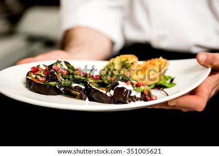 Cropped image of chef holding aubergine salad - stock photo